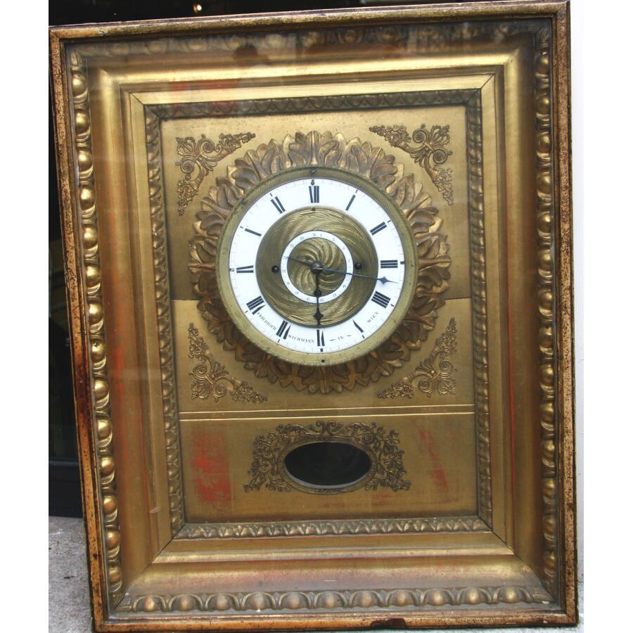 Pendule d'applique en bois doré et sculpté Vienne époque Empire signée F